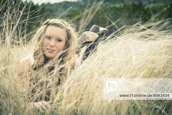 Porträt einer lächelnden jungen Frau im Gras liegend