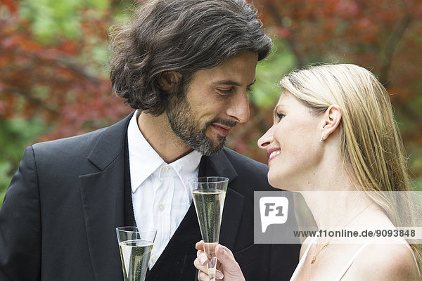 Happy bride and groom with champagne glasses in garden