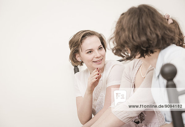 Junge Frauen in Vintage-Kleidern im Gespräch