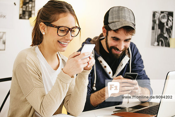 Young couple with smartphones at modern home office