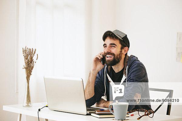 Porträt eines Mannes beim Telefonieren mit dem Smartphone im modernen Home Office