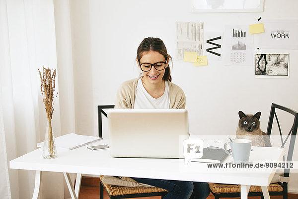 Frau und Katze am Schreibtisch sitzend