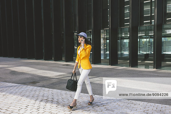 Spanien Catalunya  Barcelona  junge moderne Frau mit gelber Jacke unterwegs
