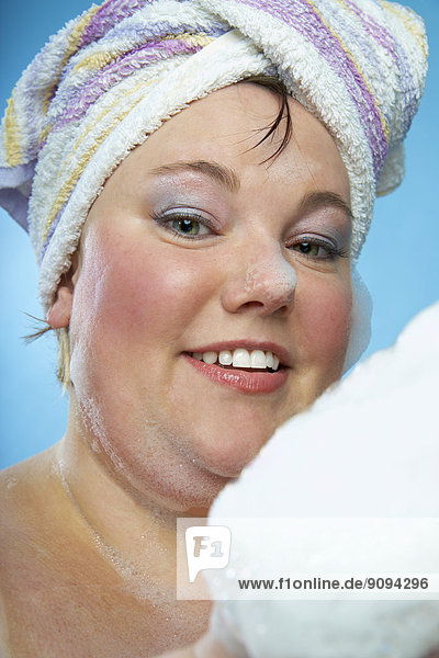 Mid-adult woman with towel turban and bathing foam