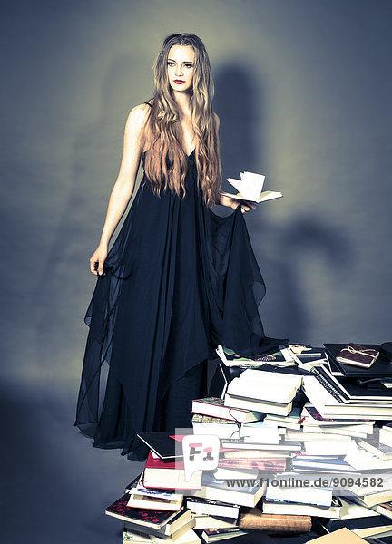 Porträt einer jungen Frau in schwarzem Abendkleid  die hinter einem Bücherstapel steht.