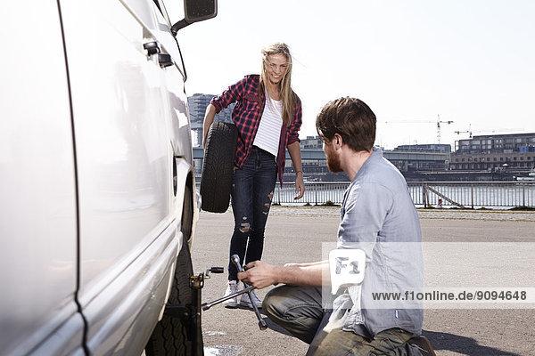 Lächelndes Paar beim Reifenwechsel im Minivan