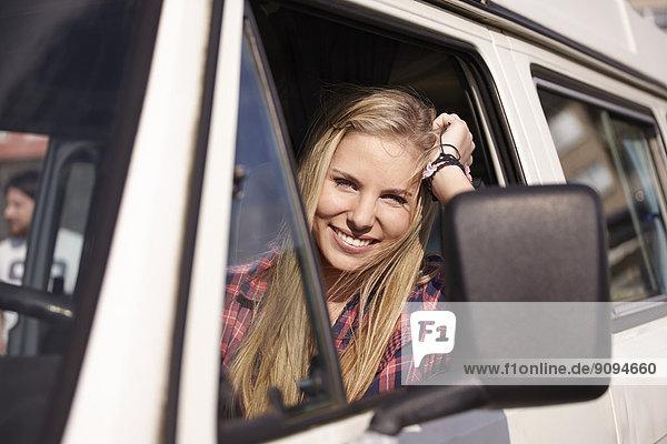 Lächelnde junge Frau im Minivan
