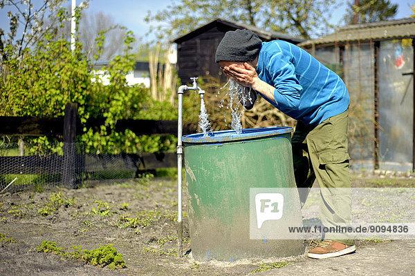 Mann wäscht sich im Garten