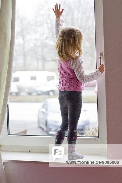 Kleines Mädchen steht auf der Fensterbank und schaut aus dem Fenster.
