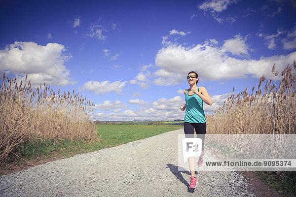 Frau joggt durch die ländliche Landschaft