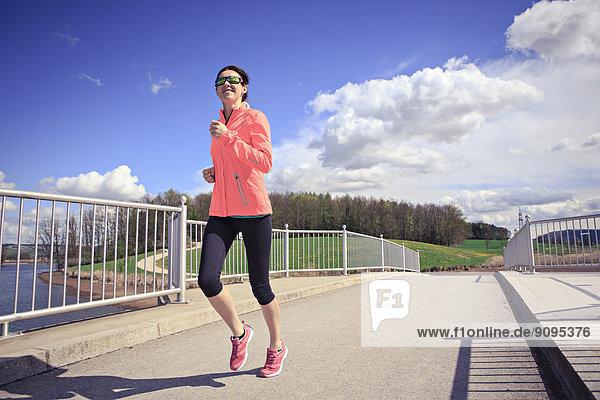 Frau joggt über eine Brücke