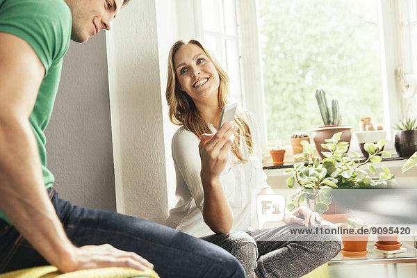 Junge Frau sitzt zwischen Pflanzen zu Hause und zeigt einem jungen Mann etwas auf ihrem Handy.
