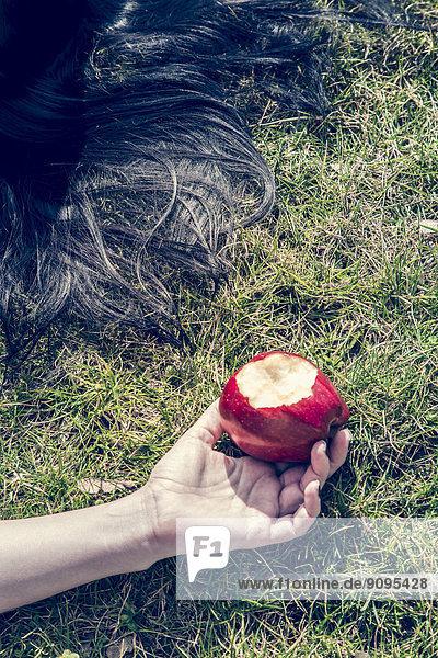 Hand der Frau auf Gras liegend mit gebissenem roten Apfel