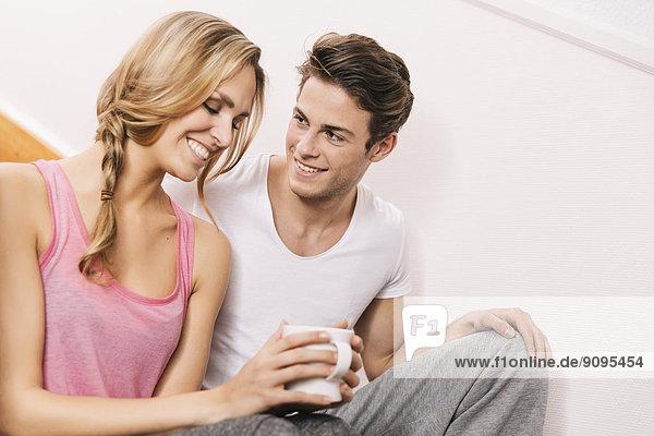 Junges glückliches Paar auf der Treppe ihres Hauses sitzend