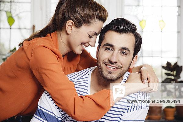 Glückliche junge Frau  die den jungen Mann zu Hause umarmt.