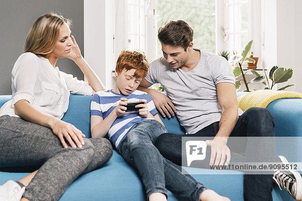 Junge Familie sitzt auf der Couch und schaut auf das Smartphone