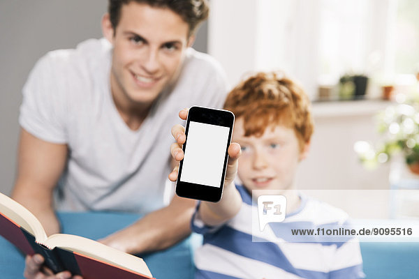 Vater und Sohn mit Buch und Smartphone