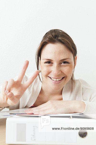 Porträt einer jungen lächelnden Frau zu Hause mit Büroarbeit