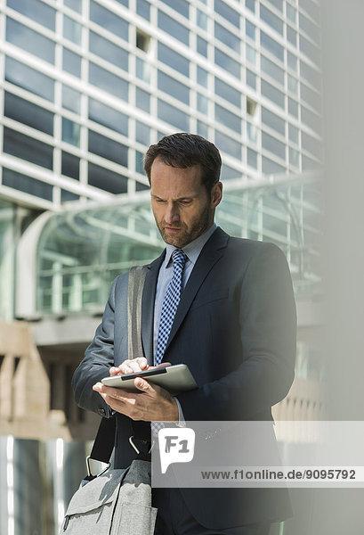 Geschäftsmann mit digitalem Tablett im Außenbereich