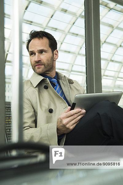 Geschäftsmann am Bahnhof mit digitalem Tablett