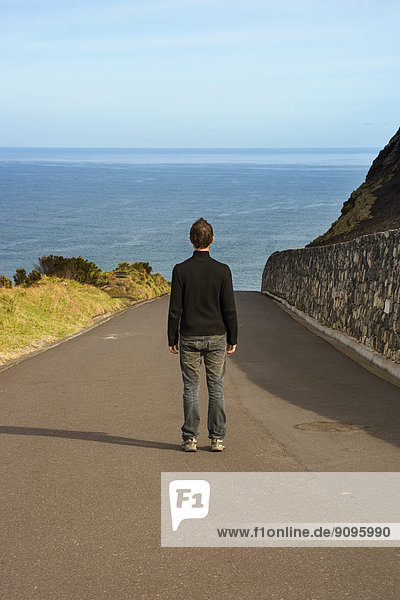 Portugal  Azores  San Miguel  man standing on street looking to the sea