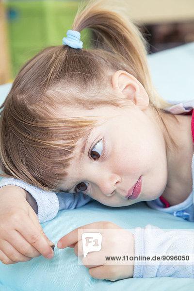 Porträt eines kleinen Mädchens auf einem Bohnensack liegend