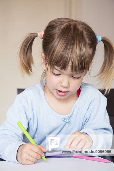Portrait of little girl painting with wax crayons