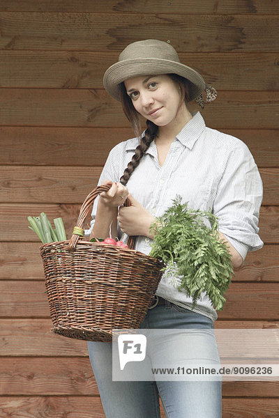 Junge Frau hält Korb mit Gemüse