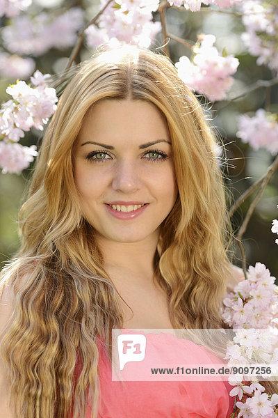Junge Frau an blühendem Kirschbaum  Portrait