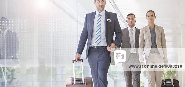 Geschäftsleute mit Koffern im Flur