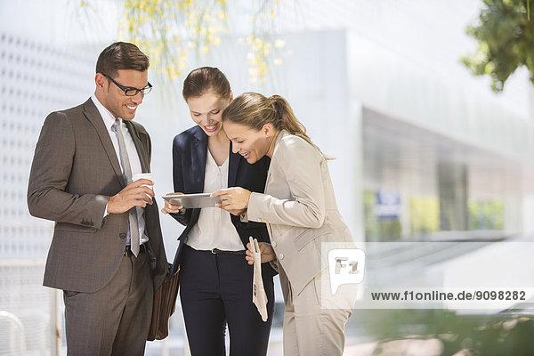 Geschäftsleute  die digitale Tabletts im Außenbereich verwenden
