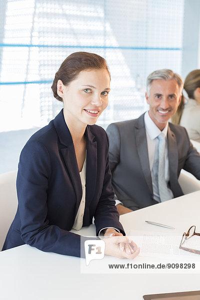Portrait von selbstbewussten Geschäftsleuten am Konferenztisch