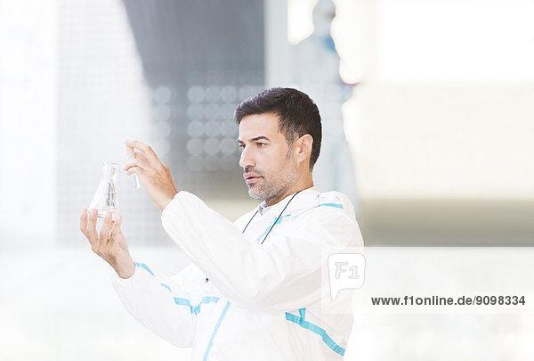 Wissenschaftler im sauberen Anzug untersucht Flüssigkeit im Becherglas