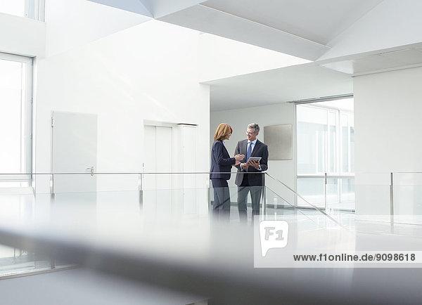 Geschäftsleute mit digitalem Tablett im Büroflur