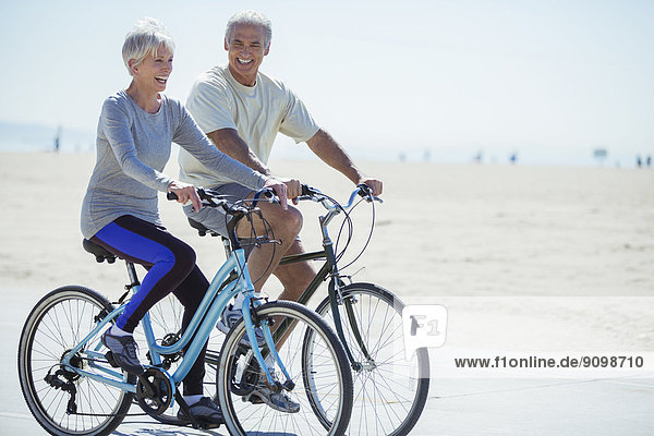 Senior couple riding bicycles on beach boardwalk