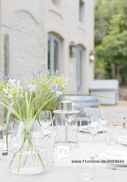 Blumenstrauß auf sonnigem Terrassentisch mit Tischdekorationen
