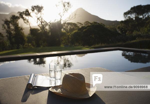 Sonnenhut  Wassergläser und Magazin auf Liegestühlen am Pool