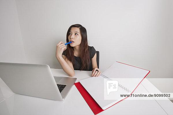 Geschäftsfrau  Schreibtisch  Notebook  Büro  jung  Nachdenklichkeit  Tagebuch