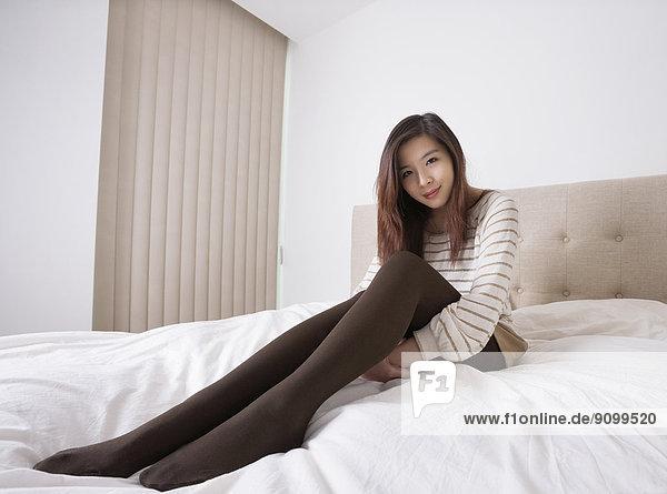 sitzend junge Frau junge Frauen Portrait Schönheit Bett Strumpfhose Länge voll