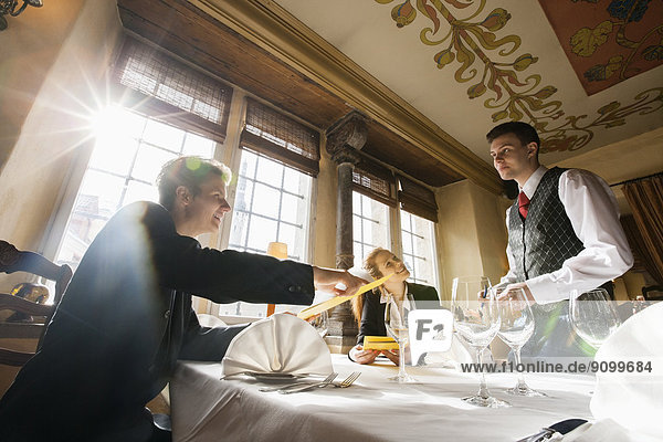 Smiling business couple ordering food at restaurant table