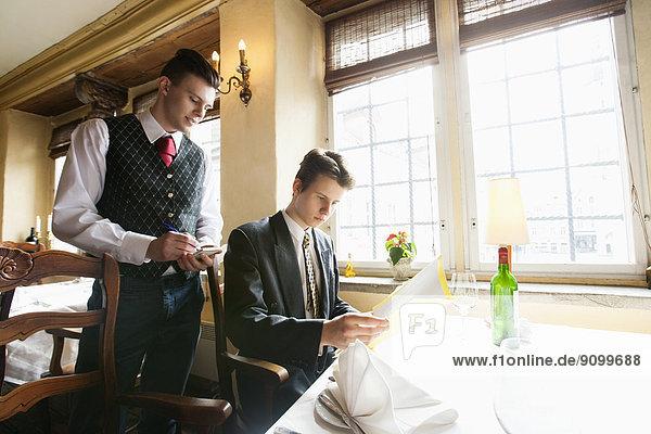 Waiter taking businessman's order at restaurant