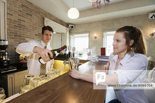 eingießen  einschenken  Wein  Restaurant  Kunde  Barkeeperin  Tresen