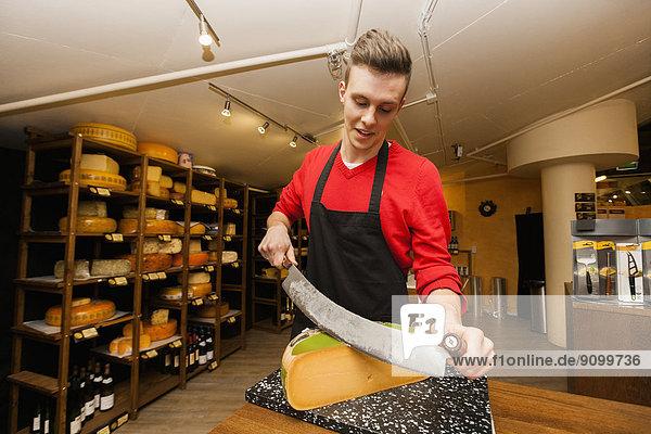 schneiden  Käse  Laden  jung  Angestellter  Tresen