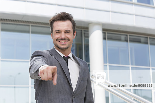 Außenaufnahme  Portrait  Geschäftsmann  zeigen  lächeln  Gebäude  Büro