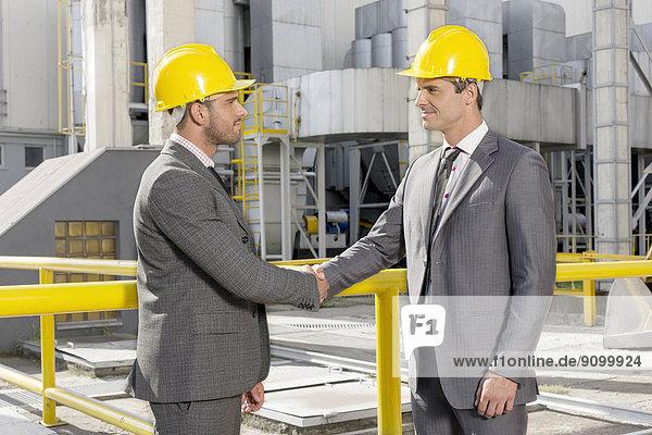 Zwei männliche Architekten Händeschütteln auf Baustelle