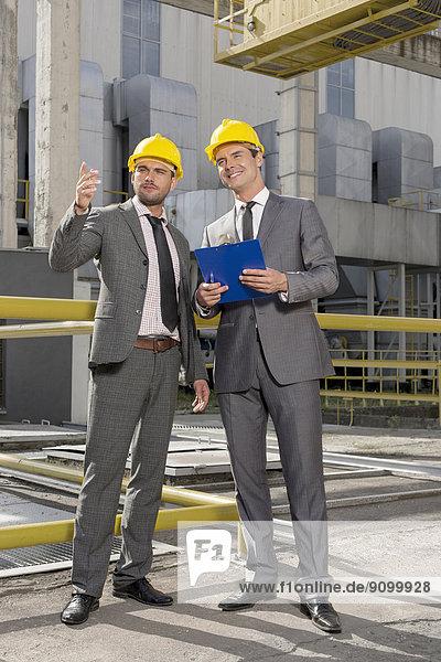 Außenaufnahme  Diskussion  Klemmbrett  Industrie  Architekt  jung  Länge  voll