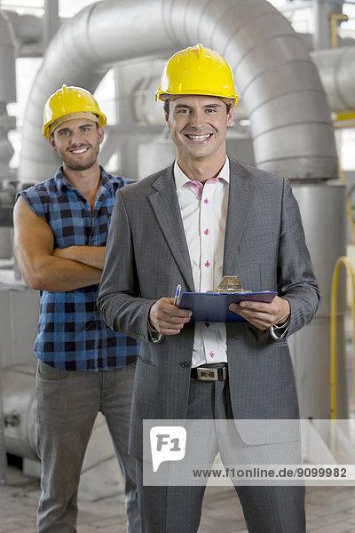 Portrait  Klemmbrett  Manager  lächeln  Industrie  arbeiten  halten  Hintergrund  jung