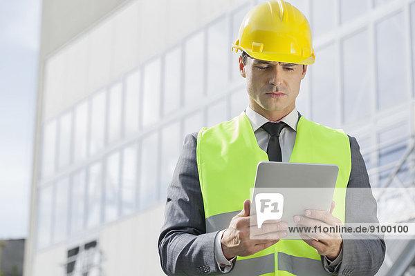 Außenaufnahme  benutzen  Bauarbeiterhelm  Industrie  Ingenieur  jung  Tablet PC  Reflektorweste