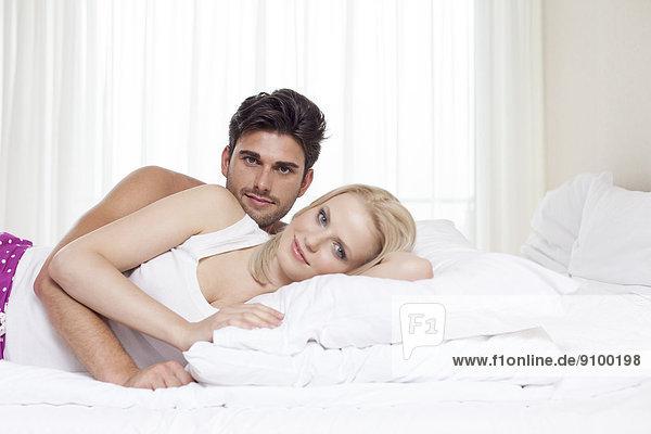 Porträt von glückliches junges Paar liegend im Bett