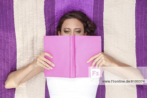 liegend  liegen  liegt  liegendes  liegender  liegende  daliegen  Frau  Buch  Decke  Picknick  über  bedecken  schießen  Streifen  gerade  Taschenbuch
